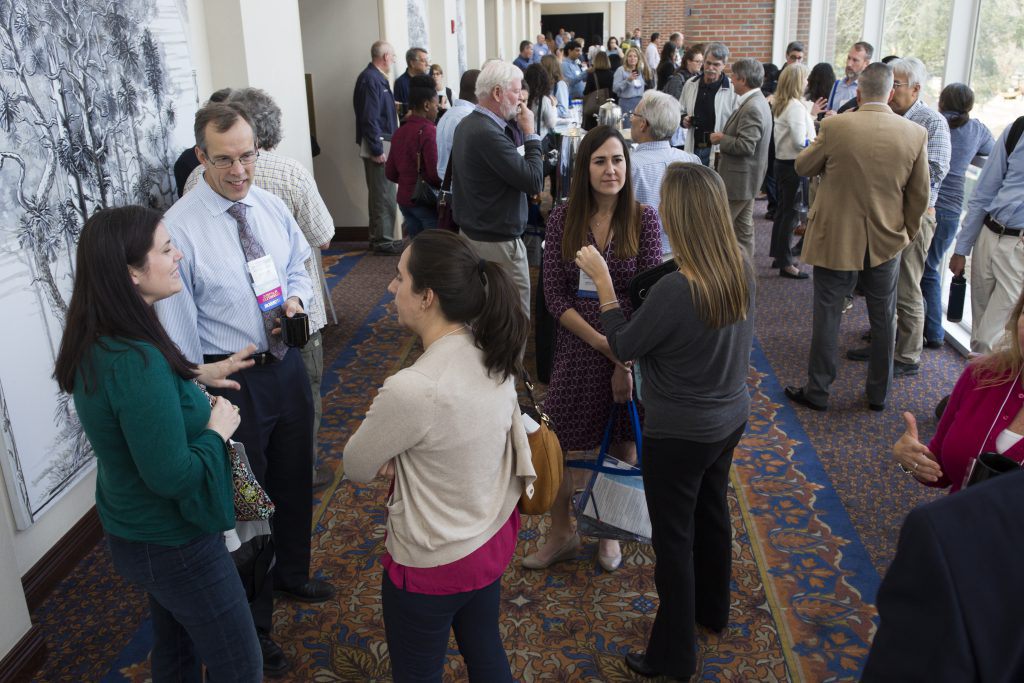 Symposium guests interacting in the North Hallway during break